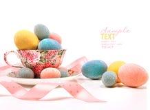 Uova brillantemente colorate in tazza di tè Immagine Stock Libera da Diritti