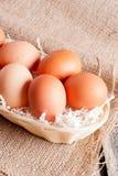 Uova in canestro di vimini su un fondo di legno Immagini Stock