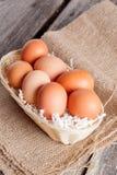 Uova in canestro di vimini su un fondo di legno Immagini Stock Libere da Diritti