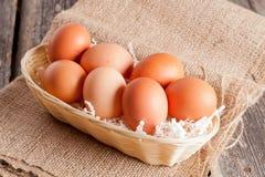 Uova in canestro di vimini su un fondo di legno Fotografie Stock