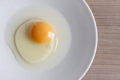 Uova che cucinano per la prima colazione, un tuorlo della forma della proteina e l'albume su un fondo bianco, o su una tavola di  Fotografia Stock