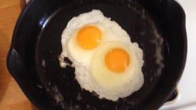 Uova che friggono in pentola del ghisa archivi video