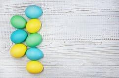 Uova colorate su un fondo di legno bianco Immagini Stock
