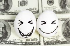 Uova con i fronti su soldi Immagini Stock Libere da Diritti