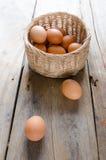 Uova con il canestro sul pavimento di legno Fotografia Stock