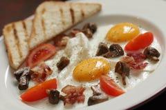 Uova con il prosciutto ed i funghi per la prima colazione Immagine Stock Libera da Diritti