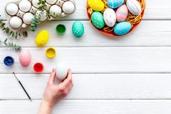 Uova con pittura variopinta per tradizione di pasqua sul modello di legno bianco di vista superiore del fondo immagini stock