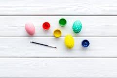 Uova con pittura variopinta per tradizione di pasqua sul modello di legno bianco di vista superiore del fondo fotografie stock