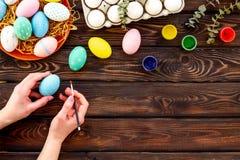 Uova con pittura variopinta per tradizione di pasqua sul modello di legno di vista superiore del fondo immagine stock
