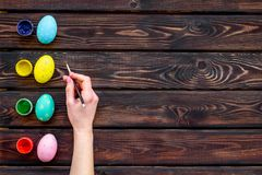 Uova con pittura variopinta per tradizione di pasqua sul modello di legno di vista superiore del fondo fotografia stock