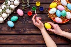 Uova con pittura variopinta per tradizione di pasqua sulla vista superiore del fondo di legno fotografia stock libera da diritti
