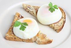 Uova cotte in camicia su pane tostato Fotografia Stock