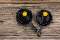 Uova crude in padella sulla vecchia tavola di legno immagini stock libere da diritti