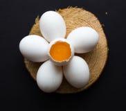 Uova crude sotto forma di margherita su un fondo scuro Fotografia Stock