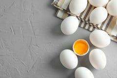 Uova del pollo in asciugamano di cucina su fondo grigio fotografie stock libere da diritti