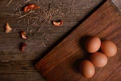 Uova del pollo sul fondo di legno rustico del tagliere Immagine Stock