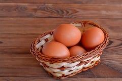 Uova del pollo in un canestro Metta le uova crude del pollo Tabella di legno Immagine Stock Libera da Diritti
