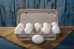 Uova dell'imballaggio su fondo di legno Fotografia Stock