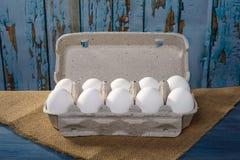 Uova dell'imballaggio su fondo di legno Immagine Stock