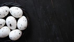 Uova dell'intero pollo in un nido su un fondo di legno rustico nero simboli di pasqua video d archivio