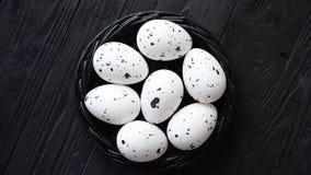 Uova dell'intero pollo in un nido su un fondo di legno rustico nero simboli di pasqua stock footage