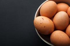 Uova di Brown in ciotola isolata su fondo scuro immagini stock