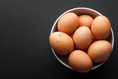 Uova di Brown in ciotola isolata su fondo scuro immagini stock libere da diritti