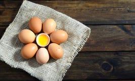 Uova di Brown su un sacco in un cerchio con l'uovo aperto nel mezzo su legno fotografia stock