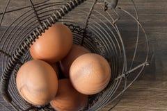 Uova di Brown in un canestro d'annata del metallo su una tavola marrone Immagini Stock
