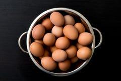 Uova di Brown in una ciotola su una tavola di legno Immagine Stock