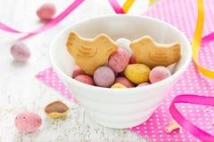 Uova di caramella del cioccolato di Pasqua e biscotti dell'uccello in ciotola su festivo Fotografia Stock