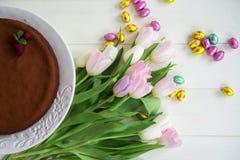 Uova di cioccolato di Pasqua, tulipani e dolce di cioccolato casalingo Immagine Stock