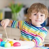 Uova di coloritura del ragazzo del bambino per la festa di Pasqua Immagine Stock