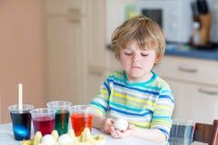 Uova di coloritura del ragazzo del bambino per la festa di Pasqua Fotografie Stock