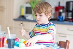 Uova di coloritura del ragazzo del bambino per la festa di Pasqua Immagini Stock