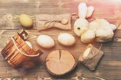 Uova di legno beige di Pasqua in secchio di legno, coniglio, ceppo di albero Fotografie Stock