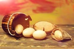 Uova di legno beige di Pasqua in secchio di legno vicino al ceppo di albero Immagini Stock