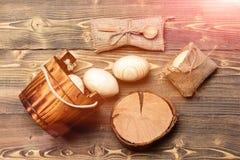Uova di legno beige di Pasqua in secchio di legno vicino al ceppo di albero Fotografia Stock Libera da Diritti
