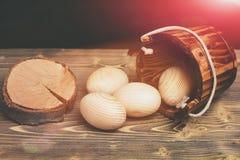 Uova di legno beige di Pasqua in secchio di legno vicino al ceppo di albero Fotografie Stock