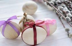 Uova di legno con nastri adesivi variopinti con il ramoscello del salice purulento sul whi Fotografie Stock Libere da Diritti