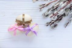 Uova di legno con nastri adesivi variopinti con il salice purulento del ramoscello sul whi Fotografia Stock