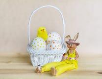 Uova di Pasqua bianche con i punti in piccolo canestro bianco Fotografia Stock