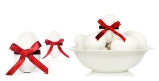 Uova di Pasqua bianche della caramella con i nastri rossi Fotografie Stock