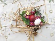 Uova di Pasqua bianche e rosse con paglia e le erbe selvagge immagini stock
