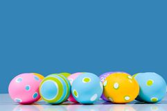 Uova di Pasqua Brillantemente colorate su priorità bassa blu con la riflessione Fotografia Stock