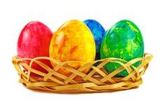 Uova di Pasqua in canestro di vimini su un fondo bianco Fotografia Stock