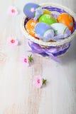 Uova di Pasqua in canestro e fiori Immagine Stock Libera da Diritti