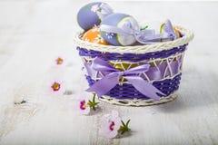 Uova di Pasqua in canestro e fiori Immagine Stock