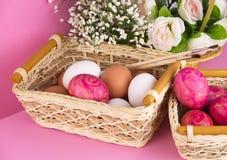 Uova di Pasqua in canestro di vimini su fondo rosa Fotografia Stock Libera da Diritti