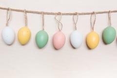 Uova di Pasqua che appendono sulla corda sopra il fondo di legno Fotografia Stock